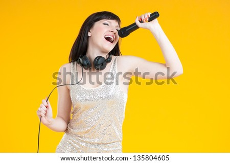 Emotional young woman singing with a microphone, horizontal shot - stock photo