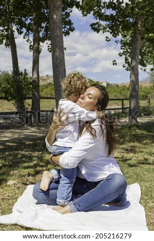 emotioned mother hugging her son on the field sitting in the floor - stock photo