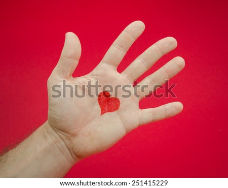Emotions and feelings from loving somebody suggested by a man's open palm with a heart over a red serious background - stock photo