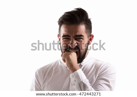 Emotions concept. Studio shot. Picture of shocked handsome man biting his wrist while posing for photographer isolated on white background. Hardlight lightening concept.