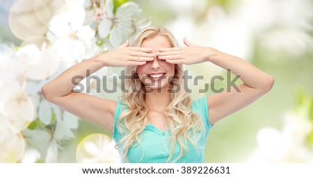 emotions, expressions and people concept - smiling young woman or teenage girl covering her eyes with palms over natural spring cherry blossom background - stock photo