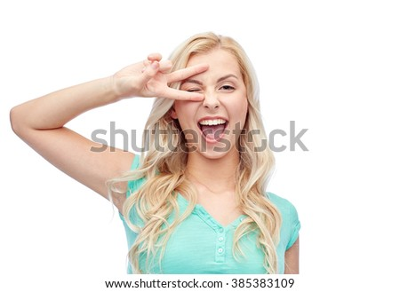 emotions, expressions, gesture and people concept - smiling young woman or teenage girl showing peace hand sign