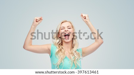 emotions, expressions, success and people concept - happy young woman or teenage girl celebrating victory over gray background - stock photo