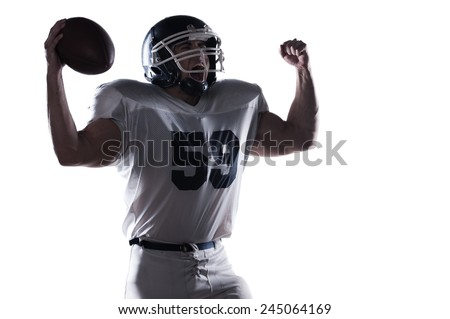 Emotions going wild.  American football player screaming and keeping arms raised while standing against white background  - stock photo