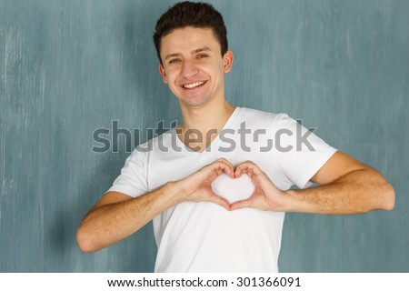Emotions man. Man showing hand sign heart on his chest. Joy, happiness, love - sincere emotions young man. Concept - for the charity, fund support world. Man making a heart shape with his hands. - stock photo