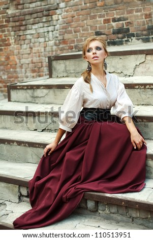 Emotions young girl sitting on the ruins of an old building - stock photo