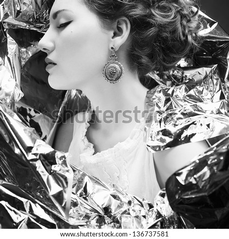 Emotive arty portrait of a fashionable queen-like young woman in white vintage dress posing over wrinkled foil background. Perfect retro hairdo. Porcelain skin. Close up. Profile. Studio shot