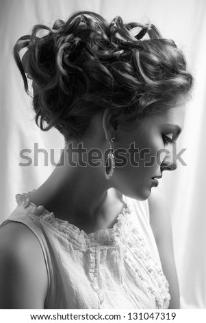 Emotive arty portrait of fashionable queen-like young woman in white vintage dress posing over white curtain background. Perfect retro hairdo. Close up. Profile. Black & white (monochrome) studio shot - stock photo