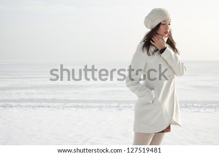 Emotive portrait of a fashionable model in white coat and beret posing at the winter seaside. Sunny weather. French style. Outdoor shot.
