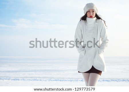 Emotive portrait of a fashionable model in white coat and beret posing at the winter seaside. Sunny weather. French style. Copy-space. Outdoor shot. - stock photo