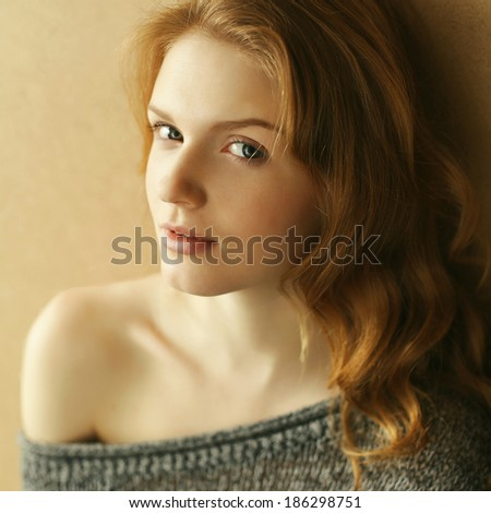 Emotive portrait of a fashionable model with ginger curly hair over the wooden background. Daylight. Close up. Studio shot - stock photo