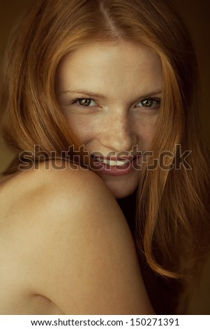 Emotive portrait of a fashionable model with red (ginger) wavy hair and natural make-up. Great white shiny smile. Perfect skin with freckles. Retro style. Close up. Studio shot