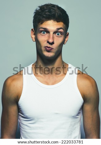 Emotive portrait of a funny handsome young man in white undershirt posing over grey background. Studio shot. Close-up - stock photo