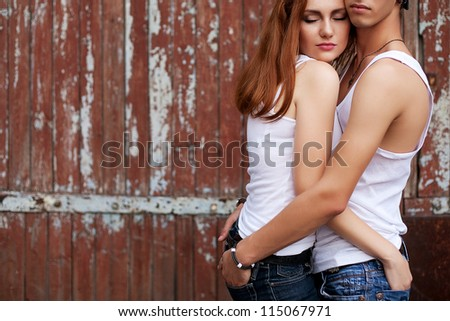 emotive portrait of a stylish couple in jeans standing together near wooden house. hands in pockets, outdoor shot - stock photo