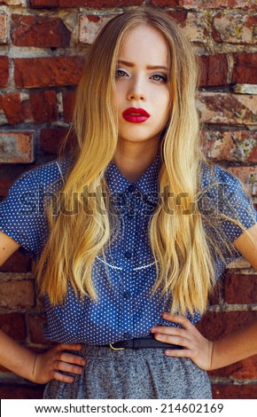 Emotive portrait of a young beautiful blond-haired girl wearing trendy blue shirt and grey skirt, posing over old brick wall.  Healthy skin with freckles, glossy hair. Outdoor shot - stock photo