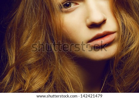 Emotive portrait of a young beautiful girl with curly long ginger (red) hair posing over black background. Perfect skin and hair. Spa salon. Close up. Studio shot