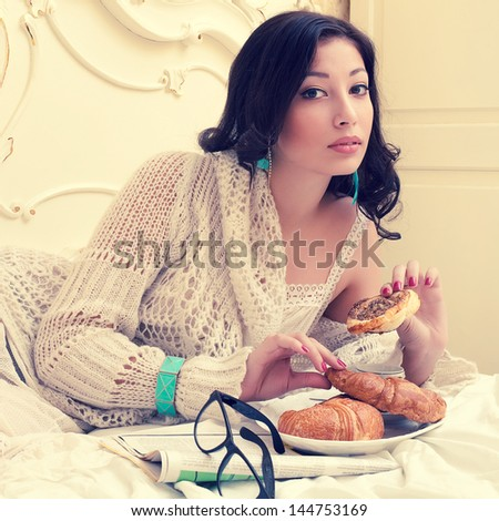 Emotive portrait of a young beautiful woman eating her croissant with strawberry jam and getting pleasure in a vintage ivory colored bedroom. Retro (classic, old hollywood) style. Indoor shot - stock photo