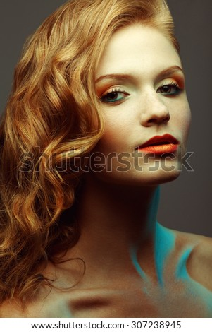 Emotive portrait of fashionable model with glossy red (ginger) curly hair and evening make-up posing over grey background. Perfect skin with freckles. Retro style. Studio shot - stock photo
