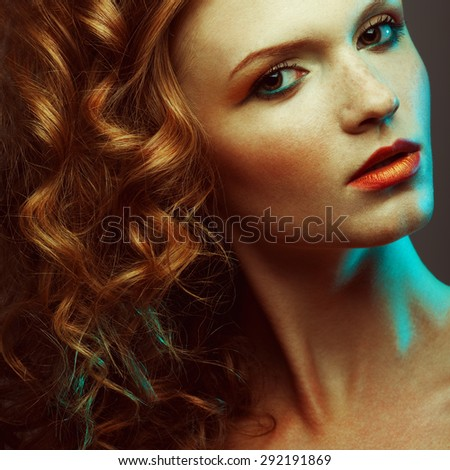 Emotive portrait of fashionable model with glossy red (ginger) curly hair and great make-up posing over grey background. Perfect skin with freckles. Retro style. Close up.  Studio shot
