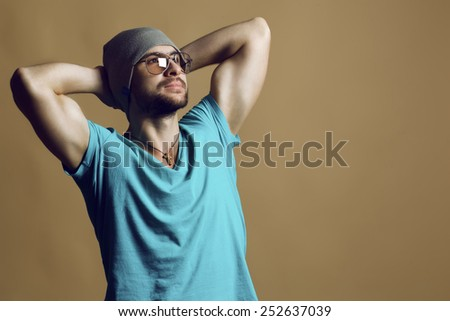 Emotive portrait of handsome man in modern glasses, hat and t-shirt with muscular hands over beige background. Copy space. Hipster style. - stock photo
