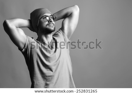Emotive portrait of handsome man in modern glasses, hat and t-shirt with muscular hands over beige background. Copy cpase. Hipster style.