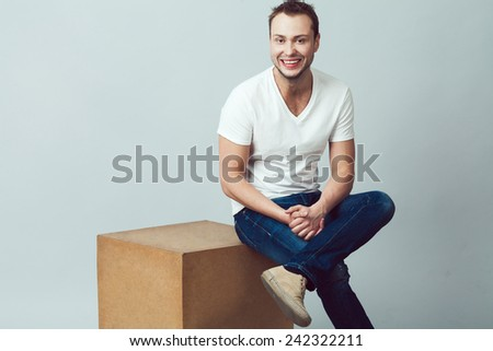 Emotive portrait of handsome young man looking at camera, wearing casual clothing & footwear, posing over gray background. White shiny smile, healthy skin. Urban style. Copy-space. Studio shot  - stock photo