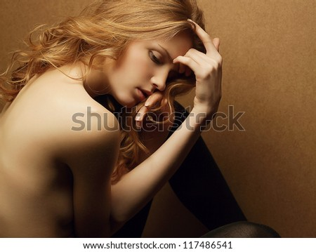 emotive portrait of young beautiful ginger red haired girl on a wooden background. studio shot - stock photo
