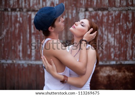 emotive portraite of a stylish couple standing near wooden house. boy holding girl's head. outdoor shot - stock photo
