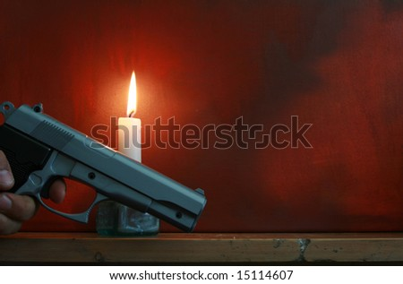 Emotive shot of a hand holding a handgun next to a candle on a mantle piece shelf. Space for copy. - stock photo