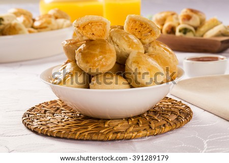 Empada Brazilian snack. pie with chicken on white plate on wooden background - stock photo