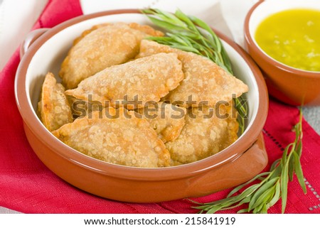 Empanadas - Spanish fried pasty filled with chorizo and cheese served with a garlic, coriander and olive oil dip. - stock photo