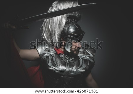 Empire, Praetorian Roman legionary and red cloak, armor and sword in war attitude - stock photo