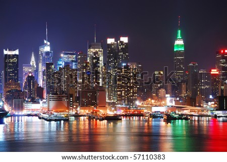 Empire State Building in New York City with Manhattan Skyline at night panorama over Hudson River with reflection.