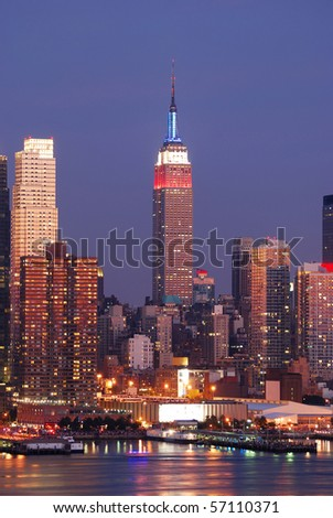 Empire State Building with New York City Manhattan skyline at dusk with skyscrapers with reflection over Hudson river. - stock photo