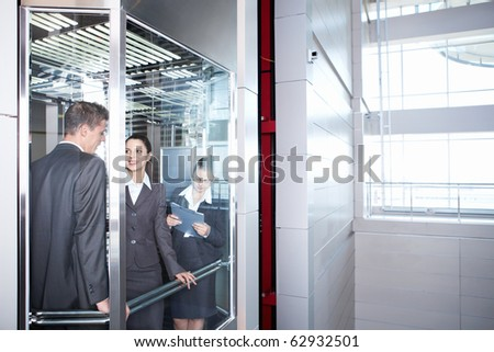 Employed people are traveling in an elevator downtown - stock photo