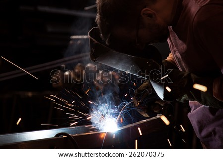 Employee at the factory welding steel tubes using MIG MAG welder.