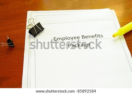 Employee benefits package on a desk with misc office supplies - stock photo