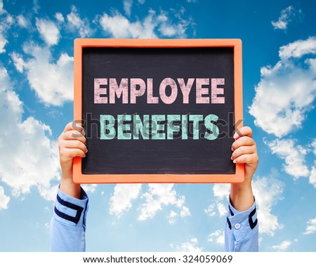 Employee Benefits word on blackboard with hands are holding.  - stock photo