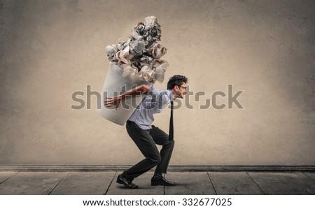 Employee carrying a huge trash bin - stock photo