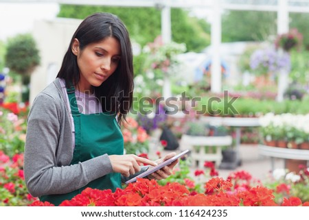 Employee checking red flowers with tablet pc in garden center thoughtfully - stock photo