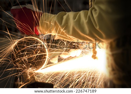 Employee cutting metal with sparks using grinder.  - stock photo
