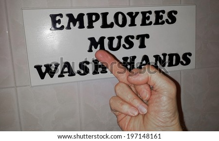 Employee giving middle finger in front of Must Wash Hands sign - stock photo