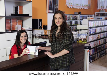 Employee handing over dvd to a costumer at the video rental store - stock photo