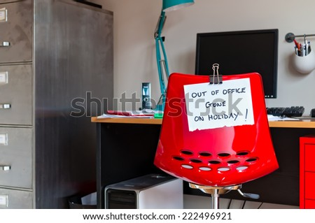 Employee leaves note on back of office chair: Out of Office. Gone on Holiday! - stock photo