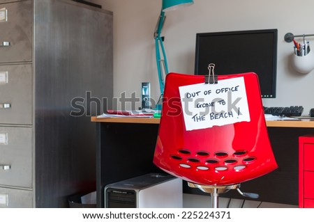 Employee leaves note on back of office chair: Out of Office. Gone to The Beach! - stock photo