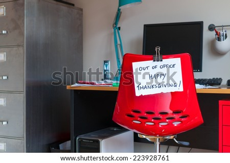 Employee leaves note on back of office chair: Out of Office. Happy Thanksgiving! - stock photo
