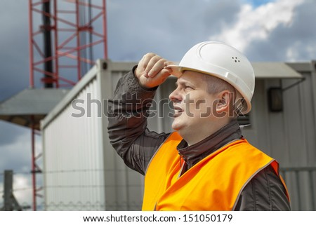 Employee near the gsm tower before the rain - stock photo