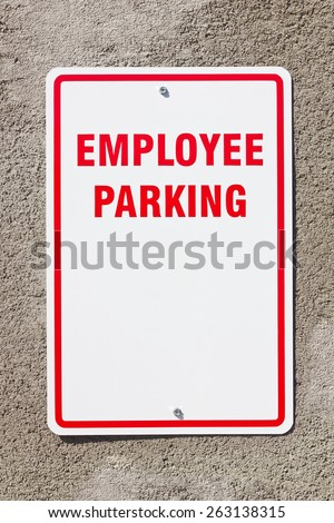 Employee parking sign with copy space hangs on a concrete wall.  - stock photo