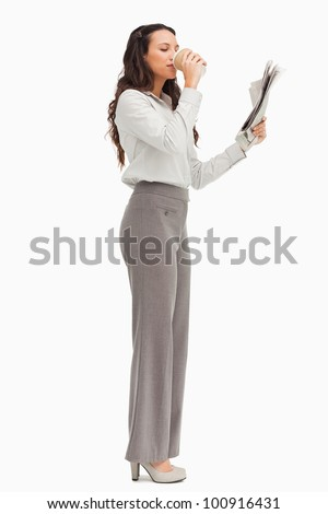 Employee reading the news while drinking a coffee against white background - stock photo