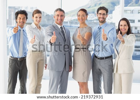 Employee's giving a thumb's up at work - stock photo